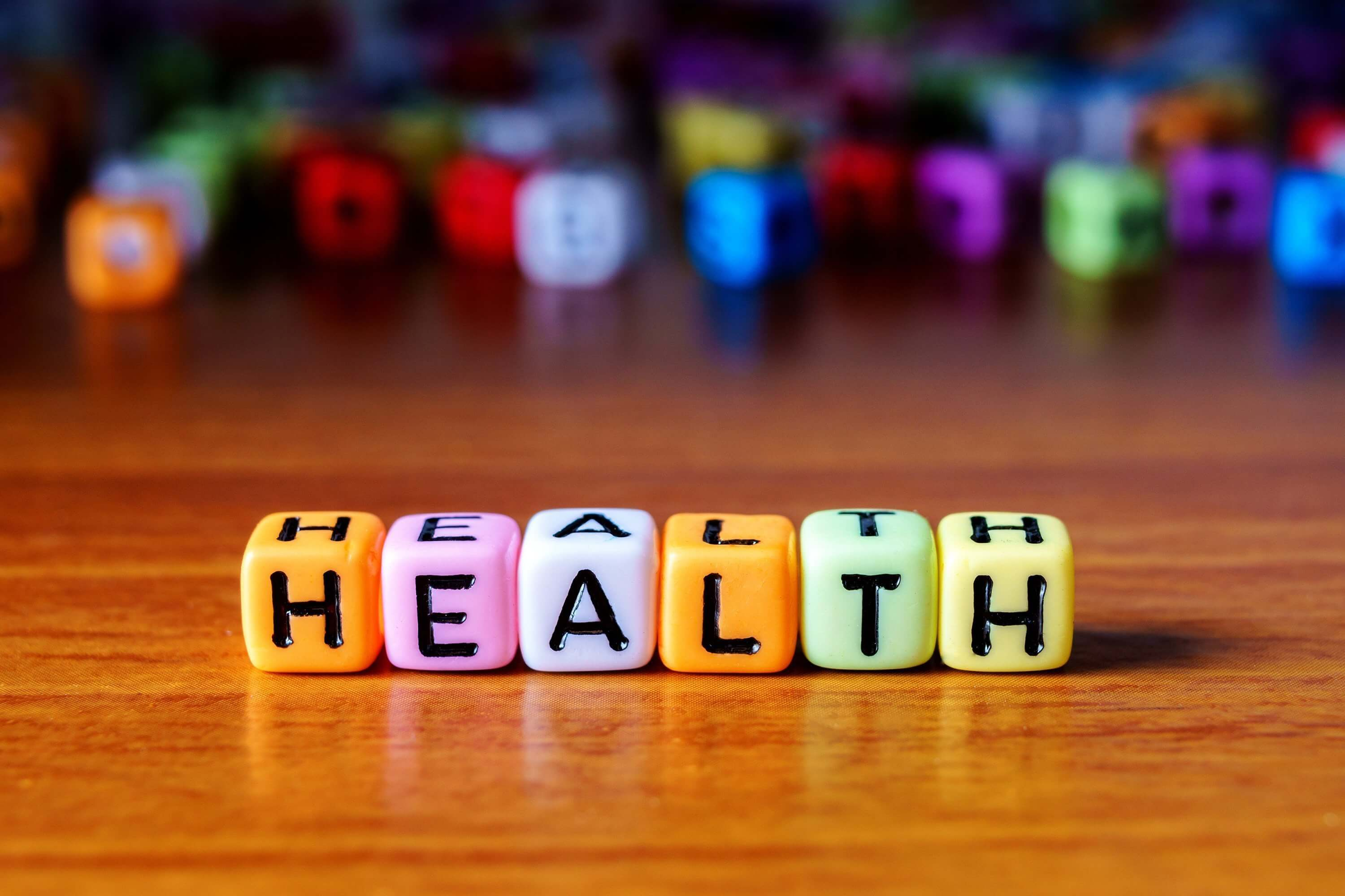 Word HEALTH spelled with colorful beads on wooden table. Read on for tips to improve patient health literacy.